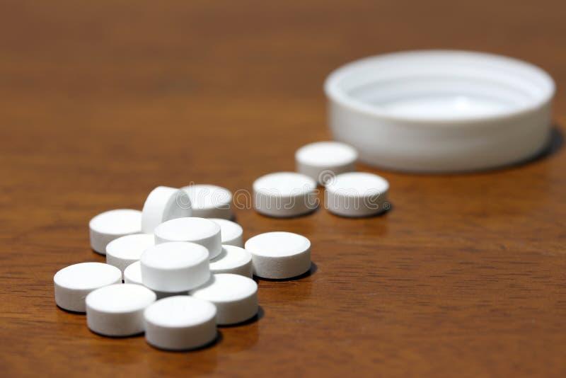 Stapel der weißen runden Medizin auf dem Bretterboden und der weißen Plastikkappe stockbild