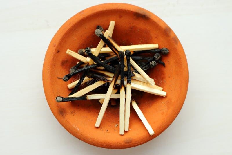 Stapel des gebrannten Matches in der orange Lehmplatte auf Draufsicht des weißen Hintergrundes stockbild