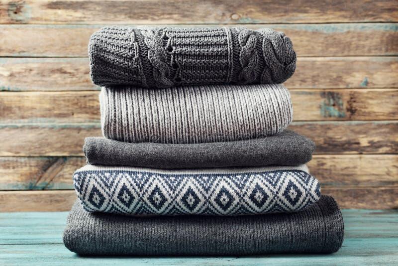 Stapel des gestrickten Winters kleidet auf hölzernem Hintergrund, Strickjacken, Strickwaren stockfotografie