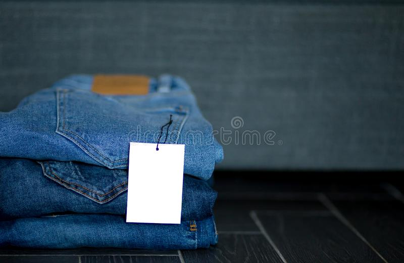 Stapel diverse schaduwen van jeans met prijsetiket Het modieuze trandy denim kleedt achtergrond royalty-vrije stock foto's