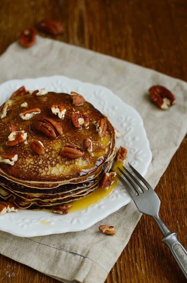 Stapel eigengemaakte dunne die pannekoeken met honing en pecannootnoten worden bedekt royalty-vrije stock fotografie