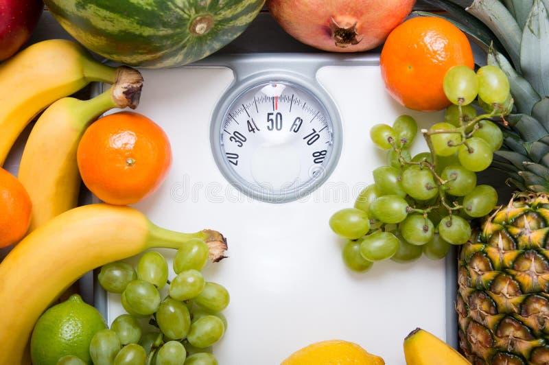 Stapel Früchte über weißer Gewichtsskala lizenzfreies stockfoto