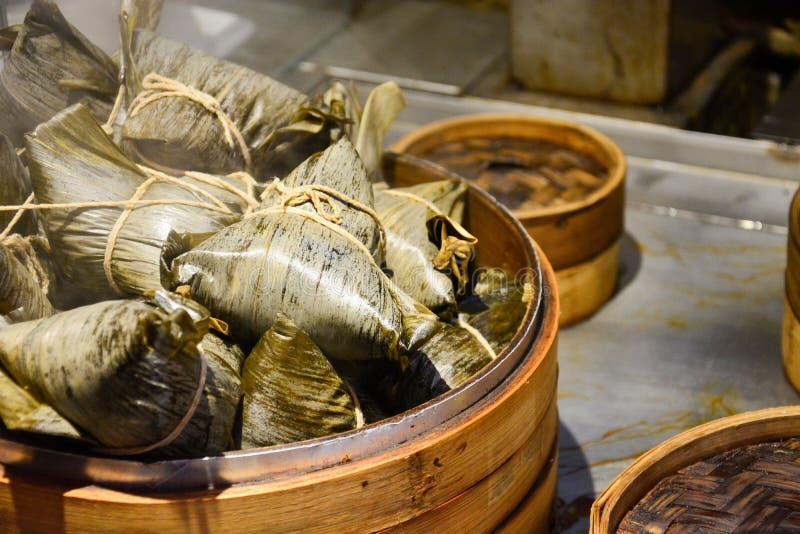 Stapel gedämpfte chinesische Mehlklöße oder zongzi im Bambuskorb, klebriger Reis eingewickelt im Bambusurlaub für Mehlkloßfestiva lizenzfreies stockfoto