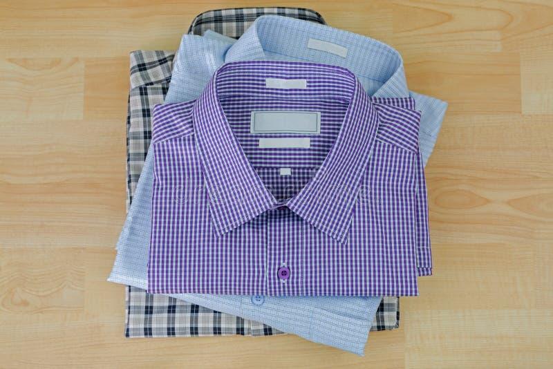 Stapel gefaltete überprüfte Kleidung, drei 3 Hemden nach gebügeltem rea lizenzfreie stockfotografie