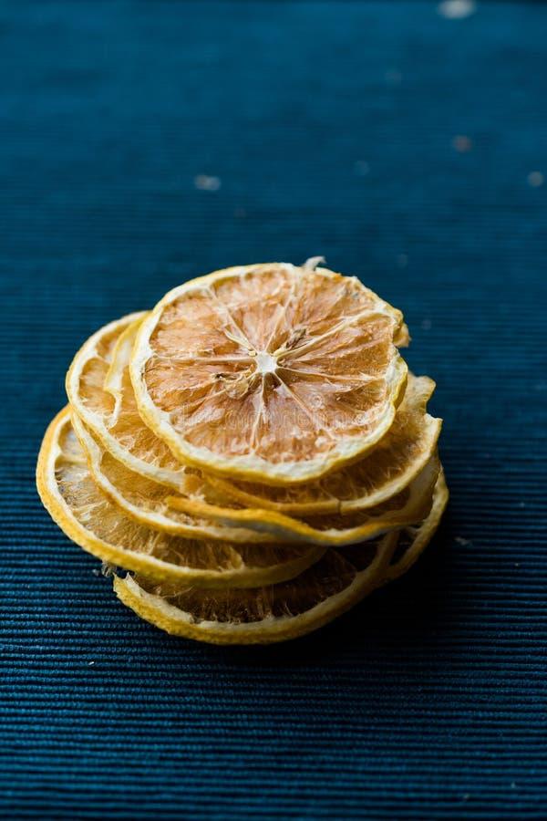 Stapel getrocknete Zitronen-Scheiben auf blauer Oberfläche/trockenes und geschnitten stockbilder