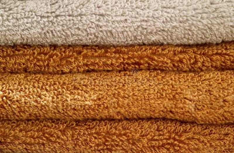 Stapel gevouwen bruine en beige pluizige badhanddoeken stock afbeelding