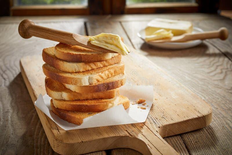 Stapel goldener knusperiger Toast mit Butterspreizer lizenzfreie stockfotos