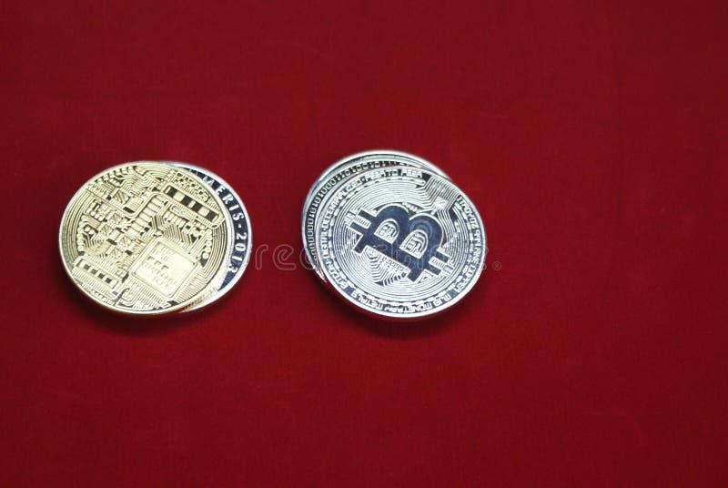 Stapel gouden en zilveren bitcoinmuntstukken op een rode achtergrond stock foto