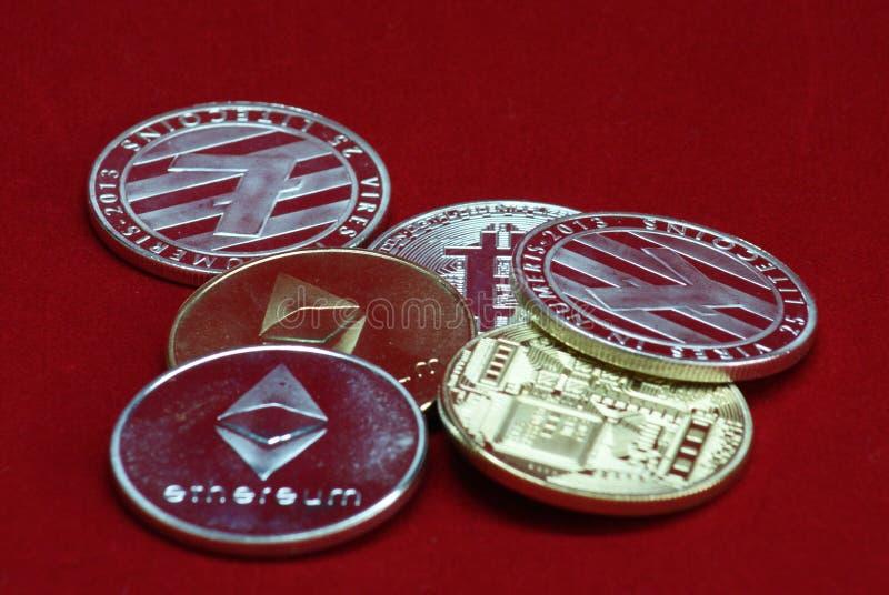 Stapel gouden en zilveren cryptocurrencymuntstukken op een rode fluweelachtergrond stock foto