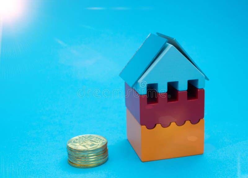 Stapel gouden muntstukken dichtbij huis met zonnepanelen stock foto