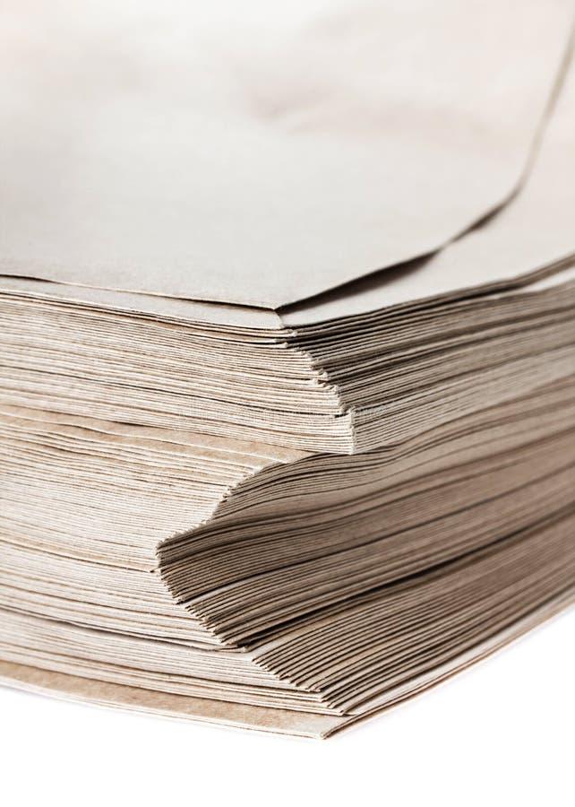 Stapel grijze gerecycleerde die document enveloppen op witte backgro worden geïsoleerd stock afbeelding