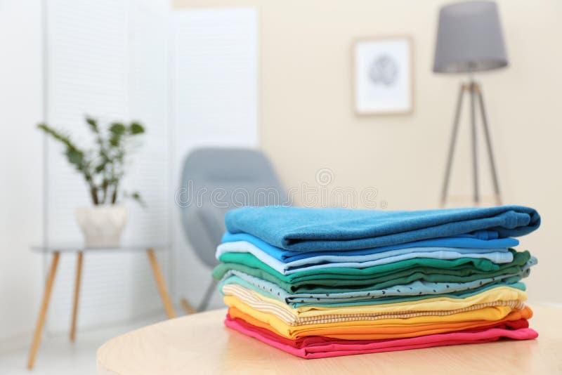 Stapel heldere gevouwen kleren op lijst binnen stock afbeeldingen