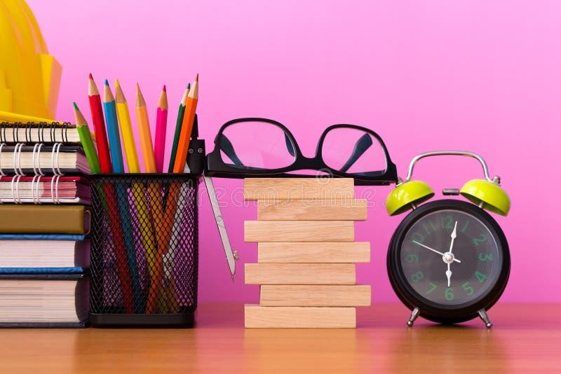 Stapel houten blokken met potloden, verdelers, glazen, bouwhelm, klok en stapel van boek op houten lijst stock foto