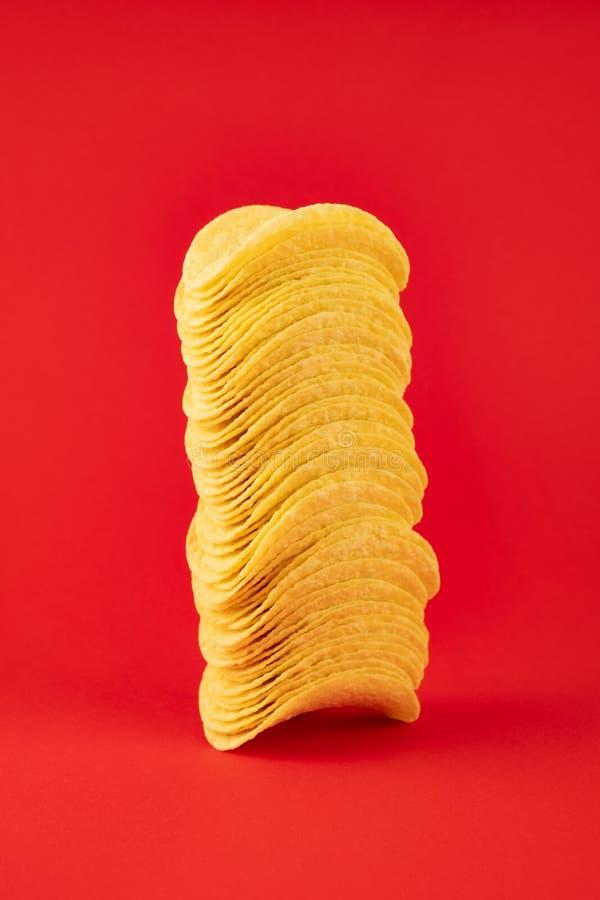 Stapel Kartoffelchips im hellen roten Hintergrund Minimalistic-ima stockfotografie