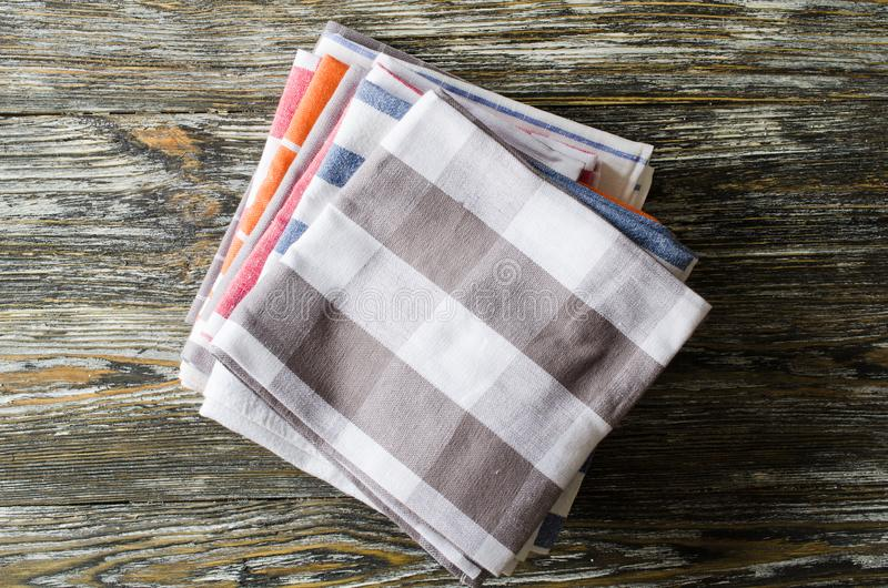Stapel keukenhanddoeken of servetten over de rustieke houten lijst stock afbeeldingen