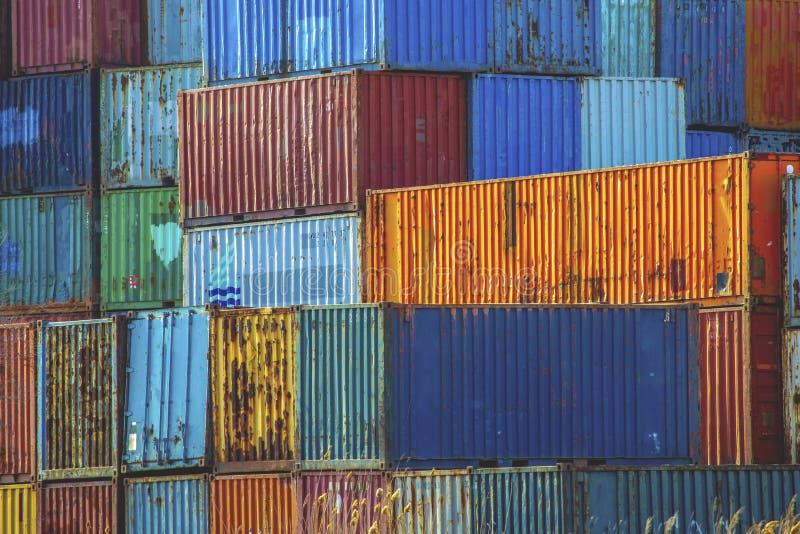 Stapel kleurrijke oude roestige overzeese vrachtcontainers in een haven stock fotografie