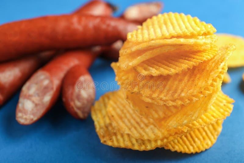 Stapel knusperige Kartoffelchips mit Würsten auf Farbtabelle stockfoto