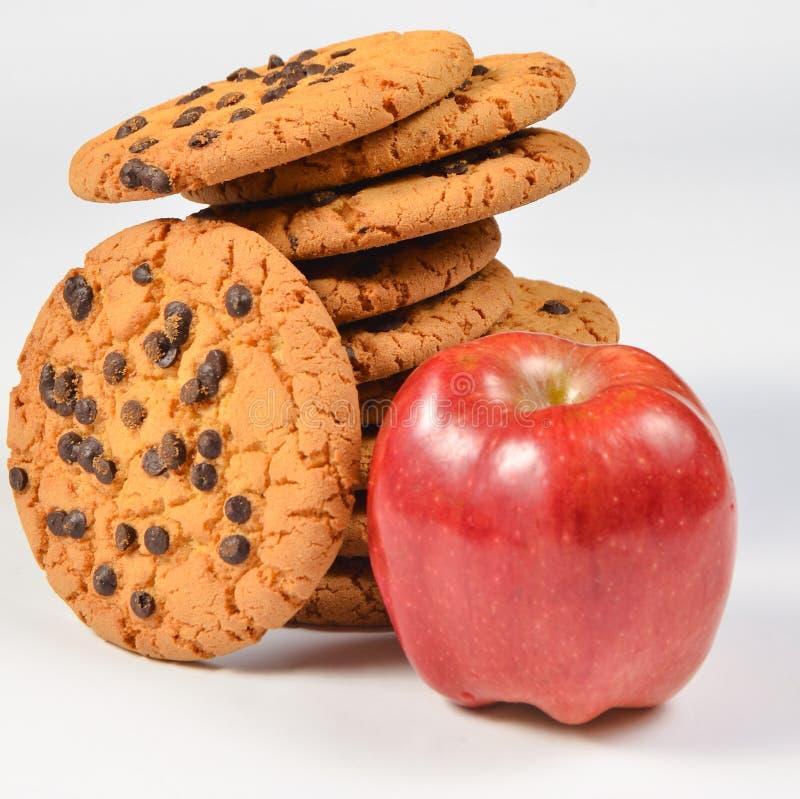 Stapel koekjes met chocolade, rode appel op een witte achtergrond royalty-vrije stock foto