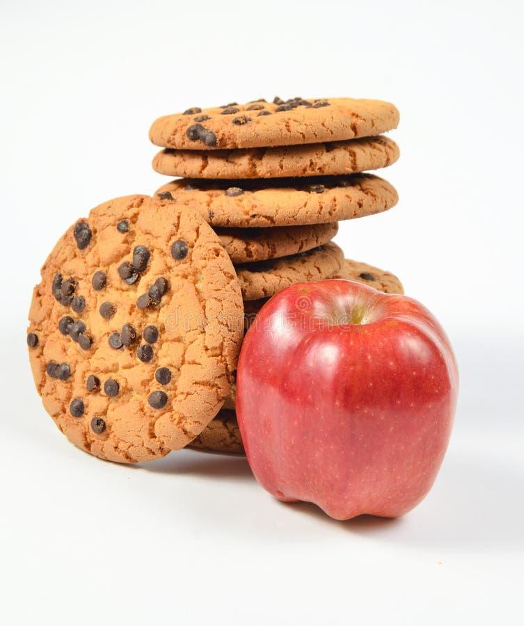 Stapel koekjes met chocolade, rode appel op een witte achtergrond royalty-vrije stock afbeeldingen