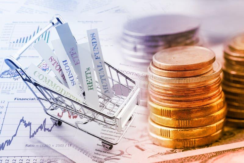 Stapel Münzen und eine Laufkatze mit verschiedenen Arten von Finanzinvestitionsprodukten stockfoto