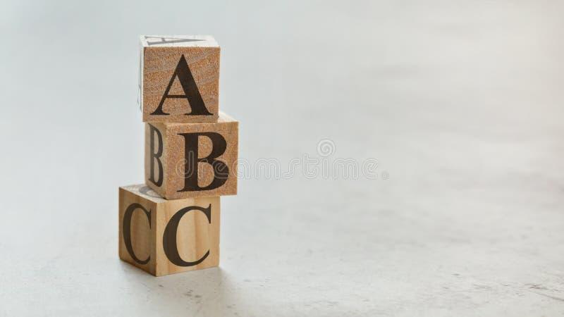 Stapel met drie houten kubussen - brieven ABC op hen, ruimte voor meer tekst/beelden op rechterkant royalty-vrije stock fotografie