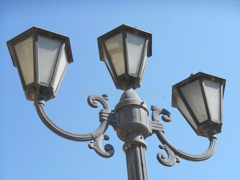 Stapel met drie straatlantaarns, blauwe hemel op achtergrond stock foto