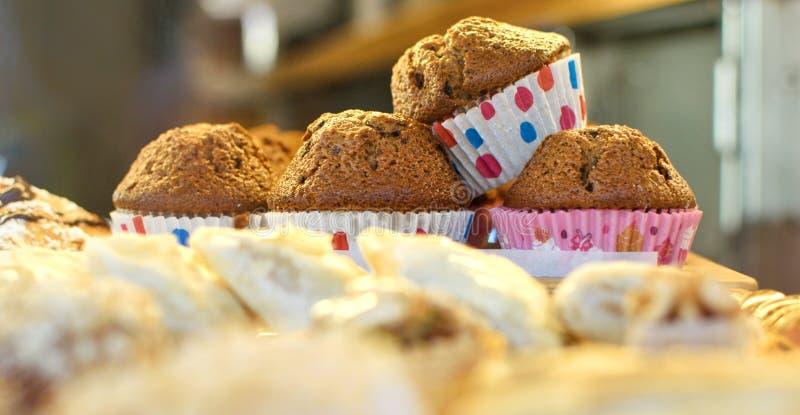 Stapel muffins op dienblad bij bakkerij worden geschikt die royalty-vrije stock afbeeldingen