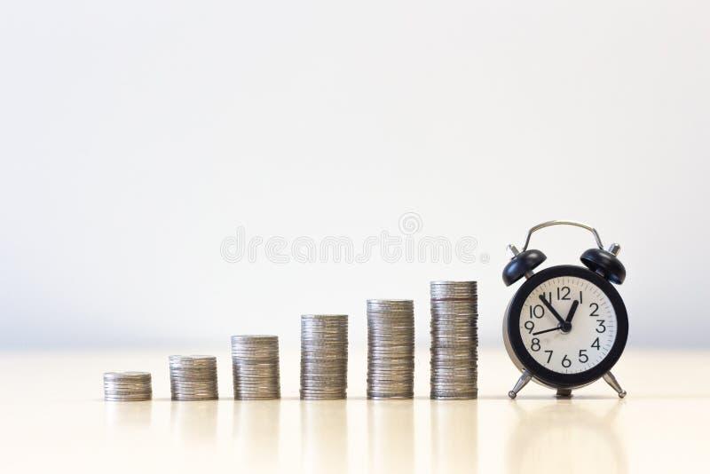 Stapel muntstukken die muntstukken met wekker verhogen royalty-vrije stock foto
