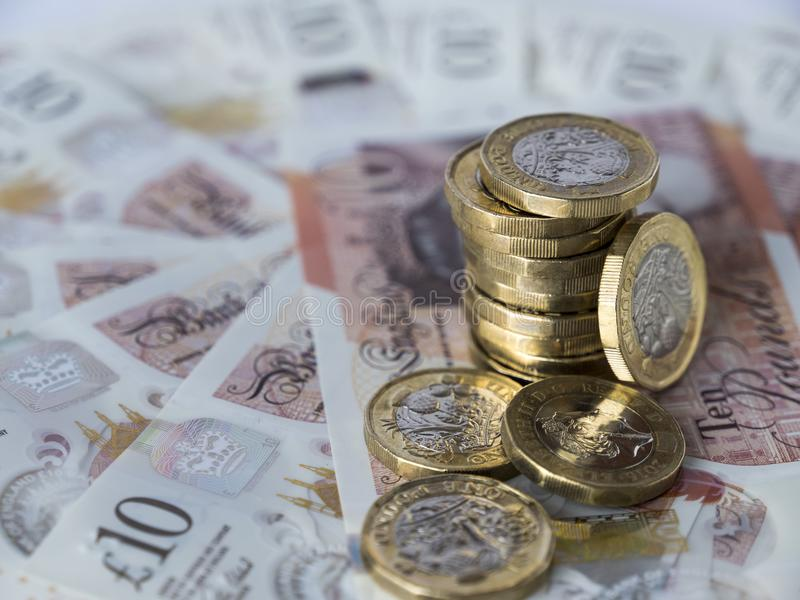 Stapel nieuwe pond Sterlingmuntstukken op semi cirkel van tien pondennota's stock afbeelding