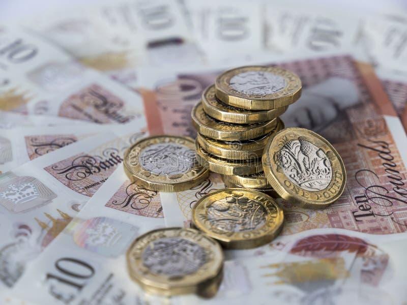Stapel nieuwe pondmuntstukken op tien pondennota's stock afbeeldingen