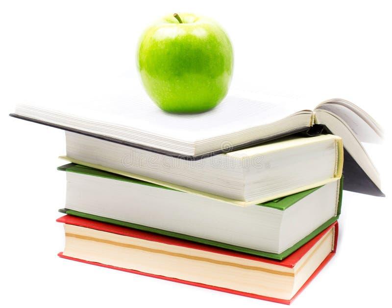 Stapel offene Bücher mit grünem Apfel auf weißem Hintergrund. Rückseite lizenzfreie stockfotografie