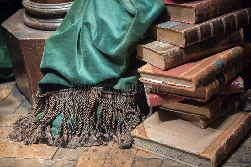 Stapel oude boeken met groen gordijn stock foto
