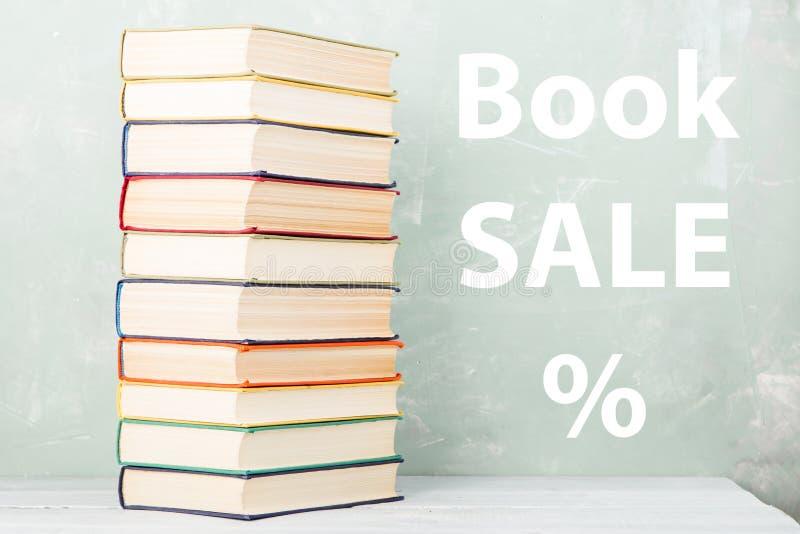 stapel oude gekleurde boeken op plank en groene achtergrond met tekst & x22; Boekverkoop %& x22; stock foto