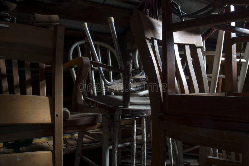 Stapel oude vergeten stoelen in zolder stock foto's