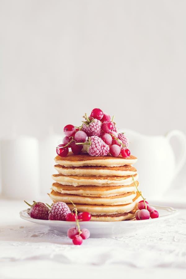 Stapel pannekoeken met framboos, rode aalbes, room en honing stock afbeeldingen