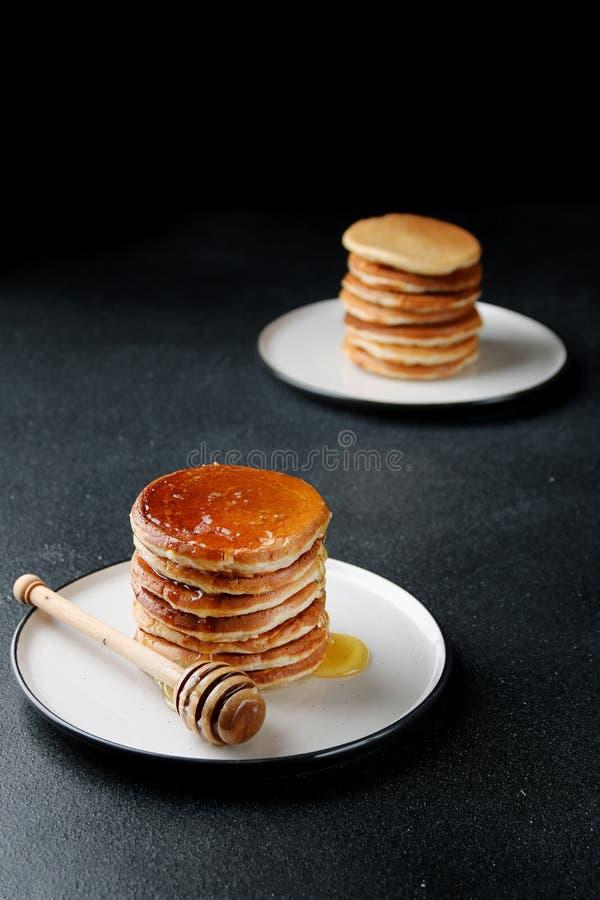 Stapel Pannekoeken met het gieten van honing op donkere achtergrond decoratieconcept en ontbijt stock foto's
