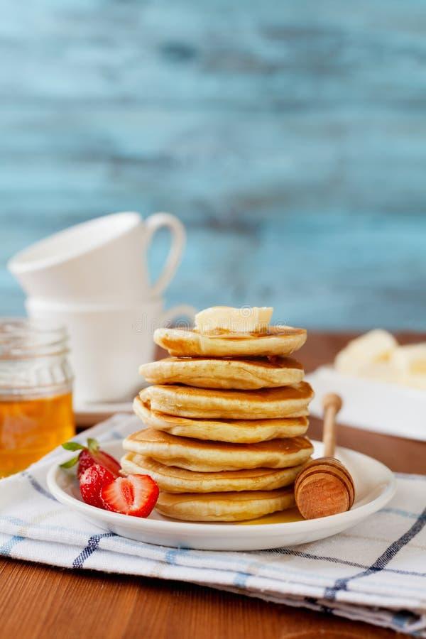 Stapel Pfannkuchen mit Honigsirup, -butter und -erdbeere in einer weißen Platte lizenzfreie stockfotografie