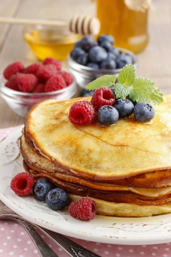 Stapel Pfannkuchen mit Sirup, Himbeeren und Blaubeeren lizenzfreie stockfotos
