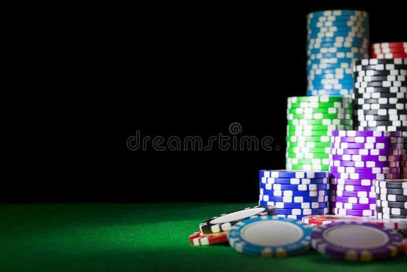 Stapel Pookspaanders op een groene lijst van de gokkenpook bij het casino Het concept van het pookspel Spelend een spel met dobbe stock fotografie