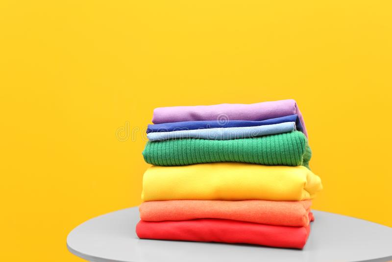 Stapel Regenbogenkleidung auf Tabelle lizenzfreie stockbilder