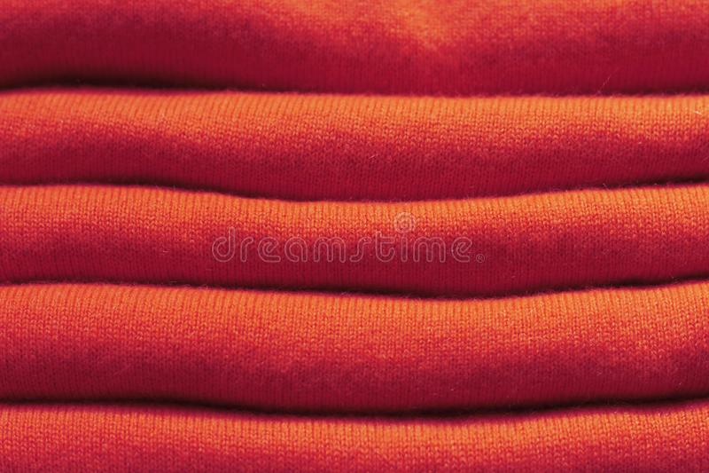 Stapel rote woolen gestrickte Strickjacken Nahaufnahme, Beschaffenheit, Hintergrund stockfotos