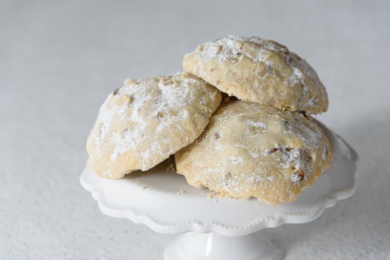 Stapel russische Tee-Kuchenplätzchen auf einer Platte des weißen Kuchens auf einem weißen Hintergrund mit silbernen Scheinen lizenzfreie stockfotografie