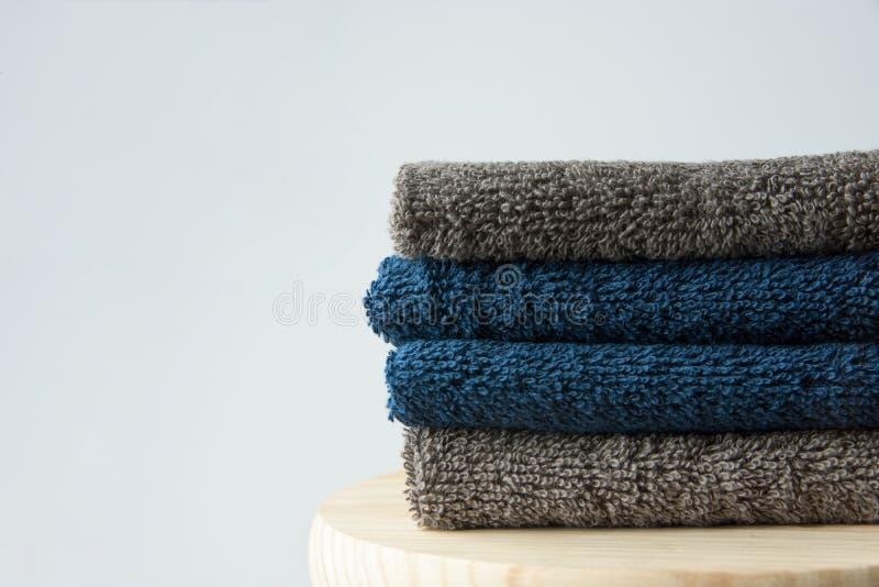 Stapel schone gevouwen marineblauwe beige badstofhanddoeken op de houten achtergrond van de klusjes grijze muur Laundry spa het c stock foto