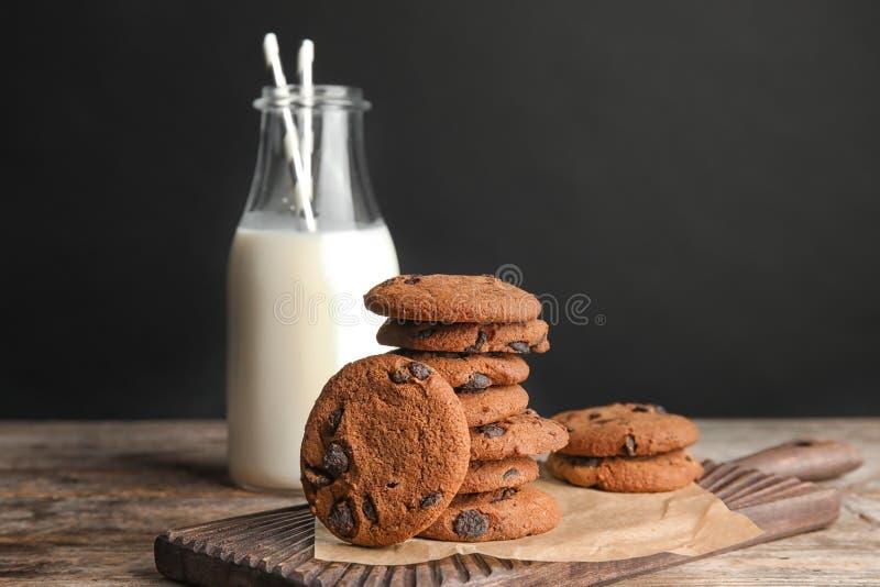 Stapel smakelijke chocoladeschilferkoekjes en fles melk stock afbeelding