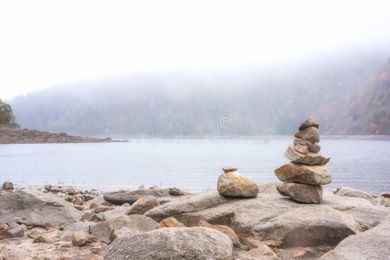 Stapel Steine neben einem Gebirgssee lizenzfreies stockbild
