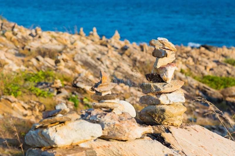 Stapel stenen op zandige overzeese strandachtergrond stock afbeeldingen