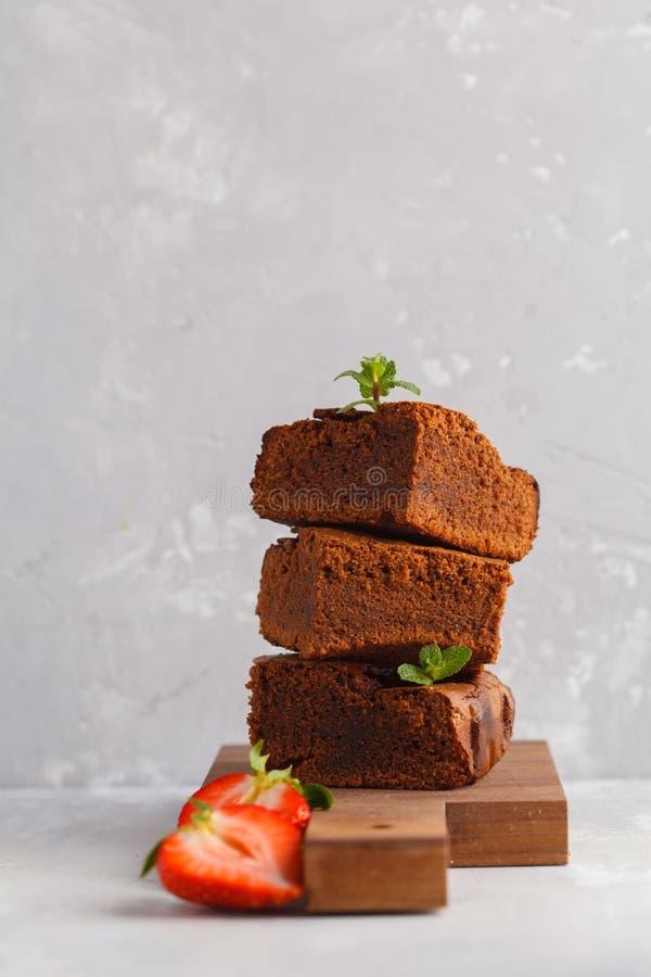 Stapel stukken van eigengemaakte donkere chocoladebrownie met strawber stock afbeeldingen