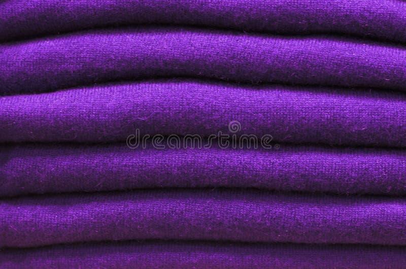 Stapel ultraviolette woolen Strickjacken Nahaufnahme, Beschaffenheit, Hintergrund der Tendenz lizenzfreies stockfoto