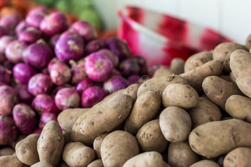 Stapel van aardappels en uien stock fotografie