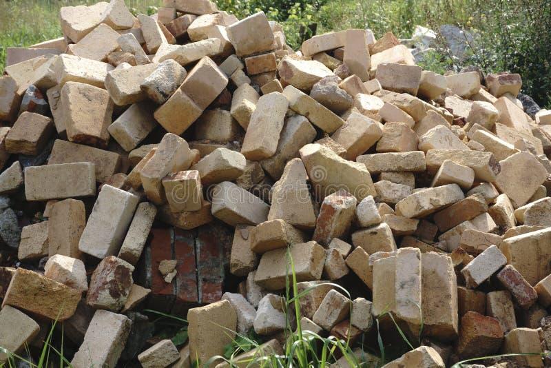 Stapel van bakstenen door een oude die bakstenen muur door een oud gebouw binnen op één van de stadsstraten wordt genomen stock afbeelding